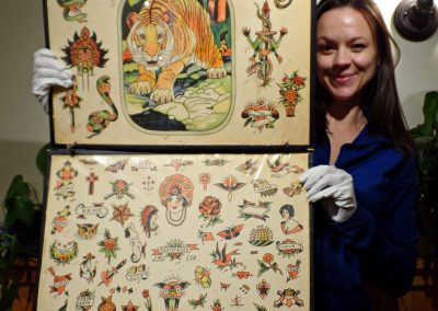 "Melissa Pitney holding the original tattoo art, ""Tiger"" and ""1941""."