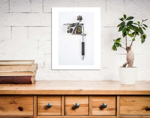 charlie geizer tattoo machine print on white wall in office room